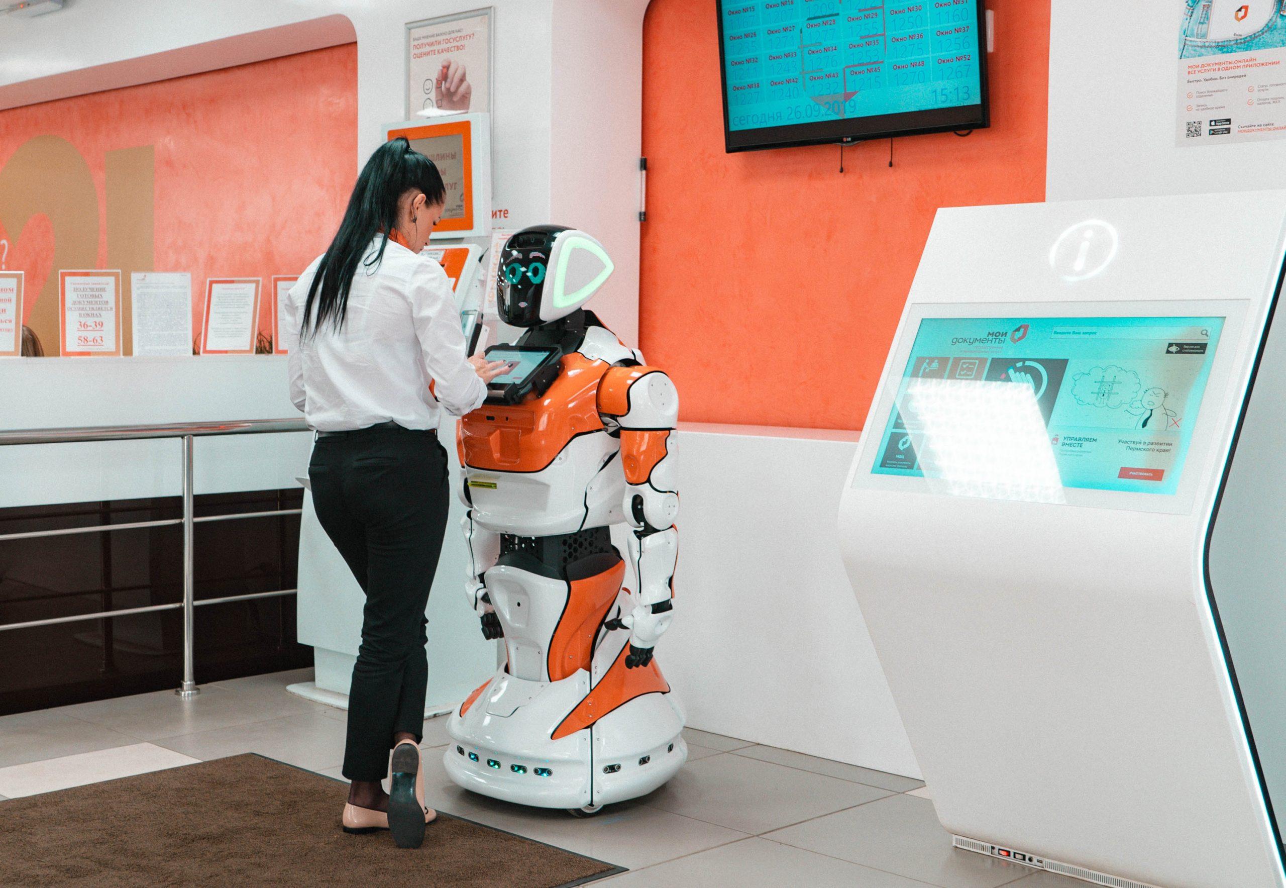 Девушка получает талон электронной очереди у робота в МФЦ