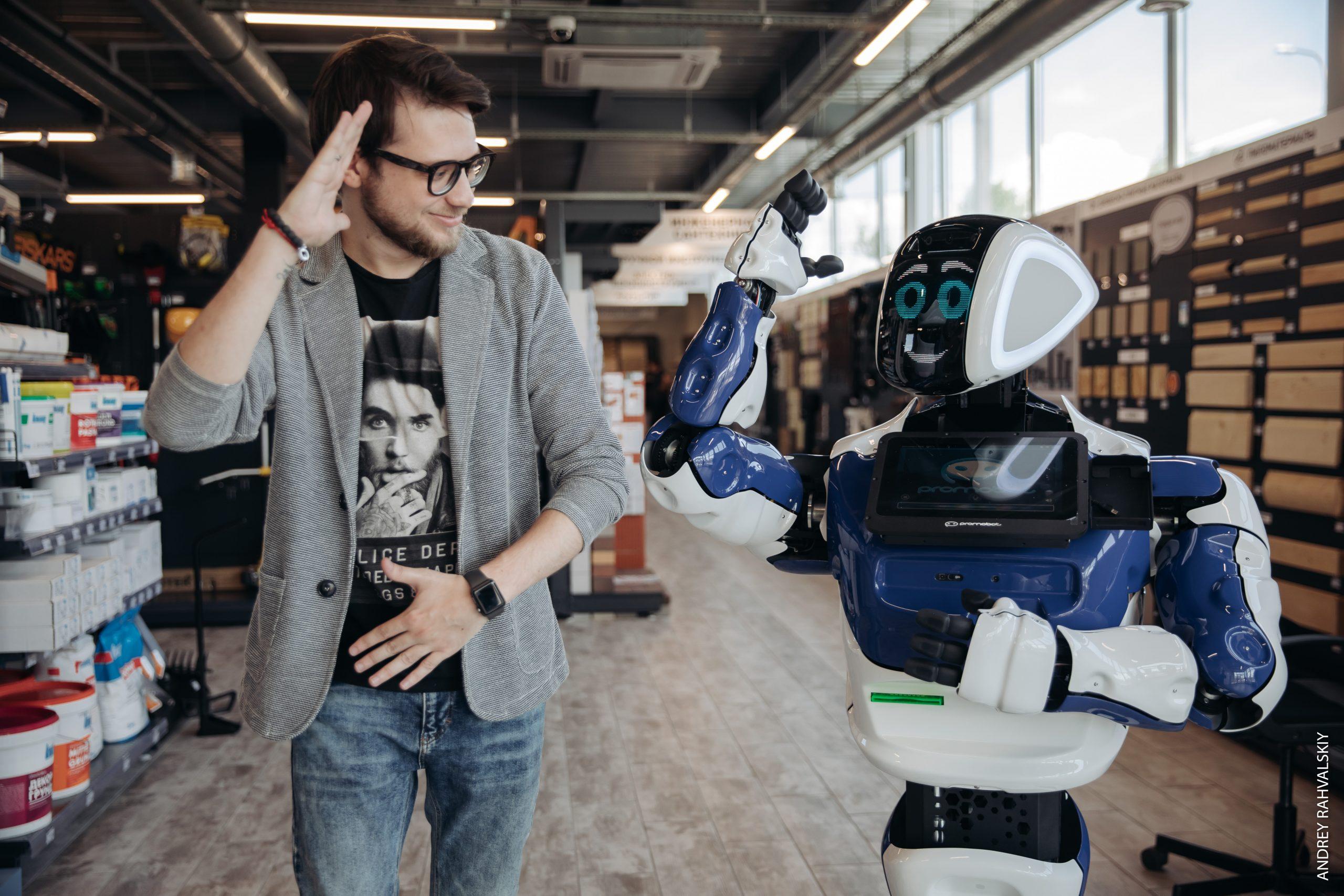 Робот промобот танцует с мужчиной в строительном магазине