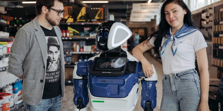 Робот промобот с мужчиной и женщиной среди полок строительного магазина